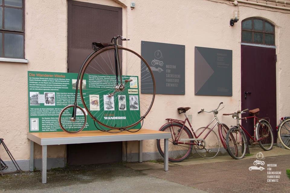 Hochrad auf Podest neben Anderen Fahrrädern