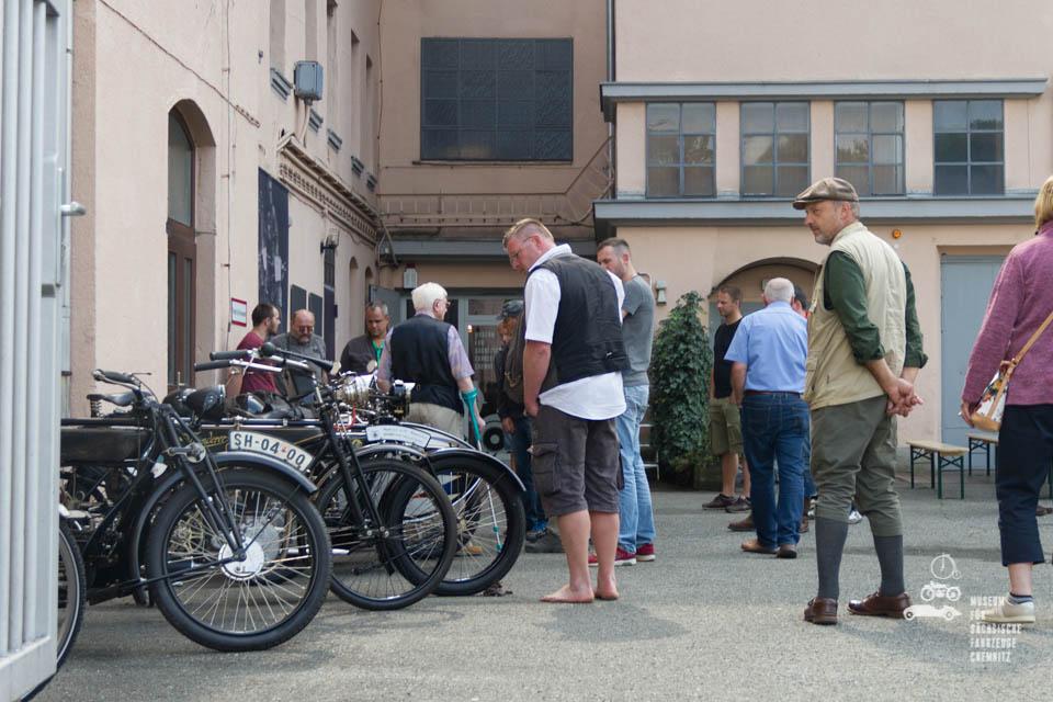 Motorräder und Besucher vor dem Museum