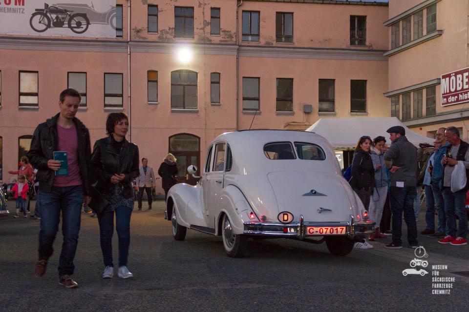 Besucher und weißer Oldtimer vor dem Museum