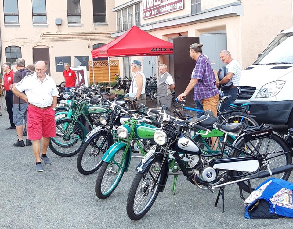 Kleinmotorräder und Besucher vor dem Museum
