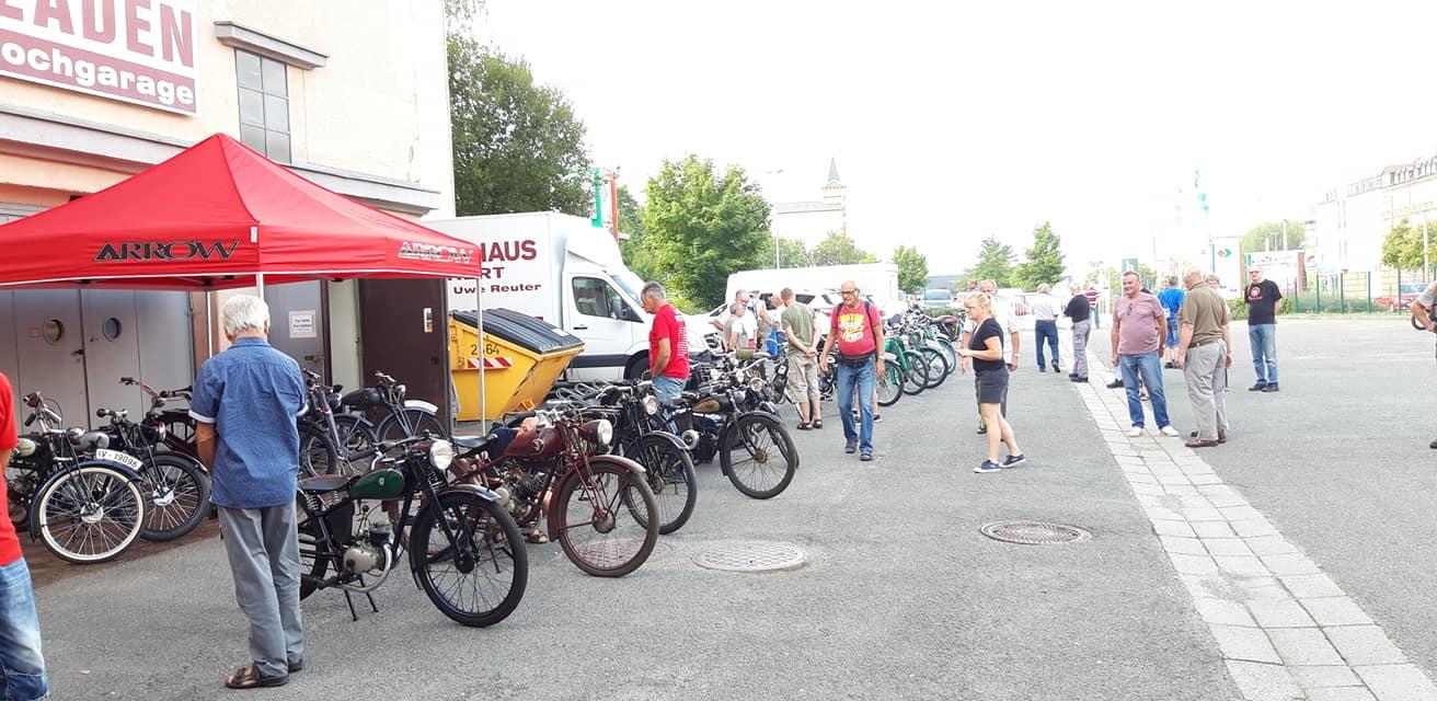 Kleinmotorräder in Reihe vor dem Museum mit Besuchern