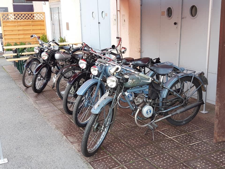 verschiedene Kleinmotorräder in Reihe vor dem Museum