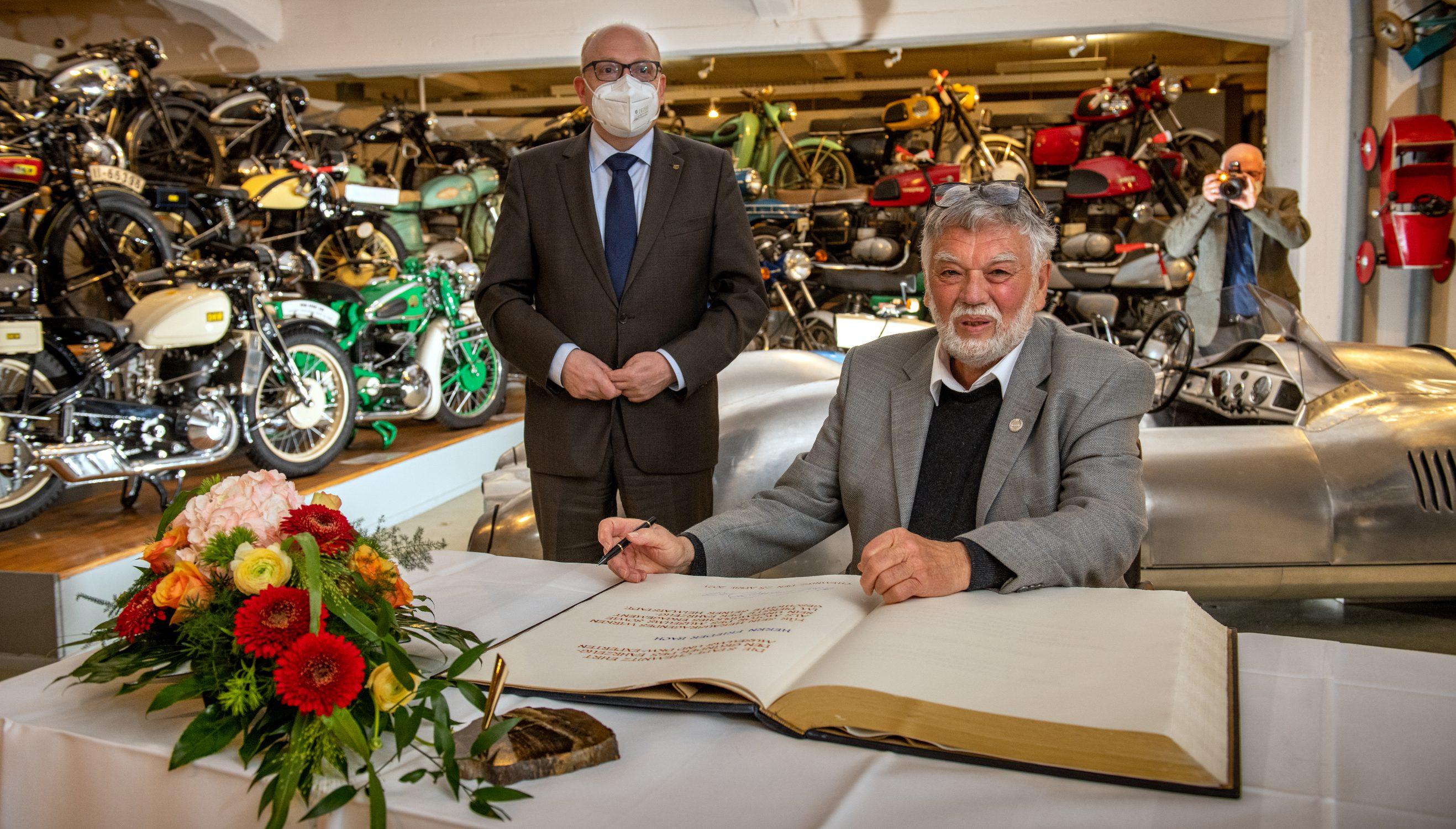 Frieder Bach sitzt vor dem Goldenen Buch, im Hintergrund steht Sven Schulze
