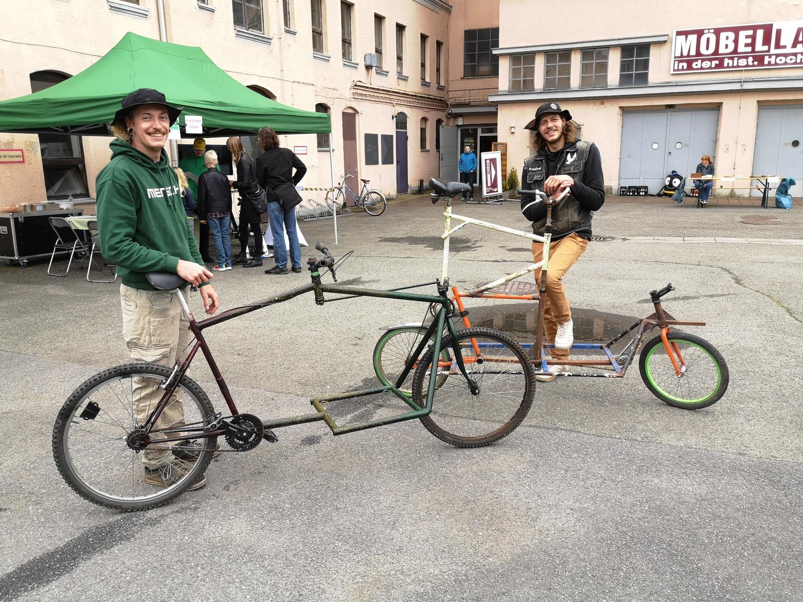 Zwei selbstgebaute Räder mit ihren Besitzern